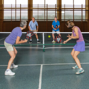 Rhino 2-Player Edge Wooden Pickleball Paddle with players playing pickleball